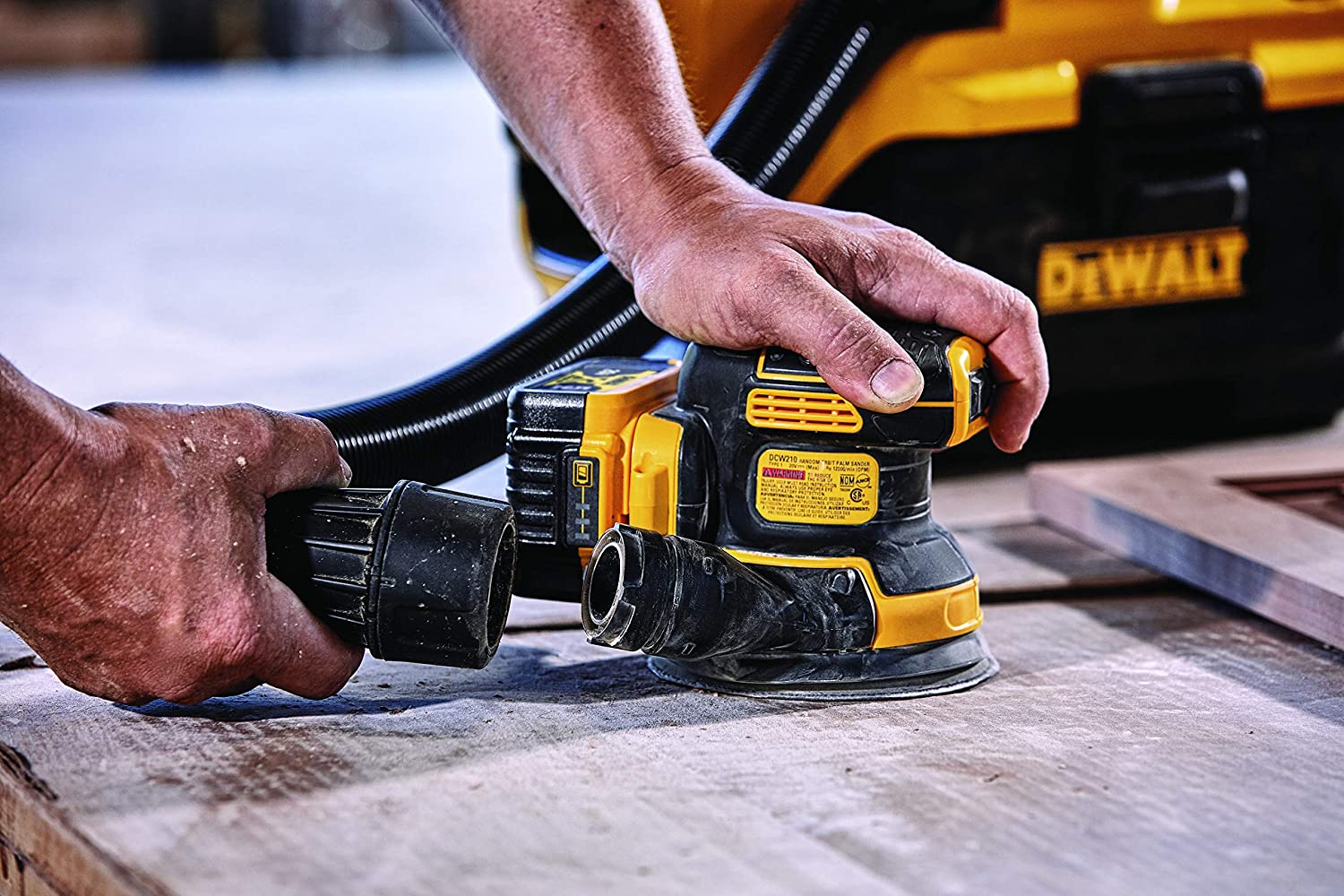 wood worker attaching exhaust pipe to rotary sander